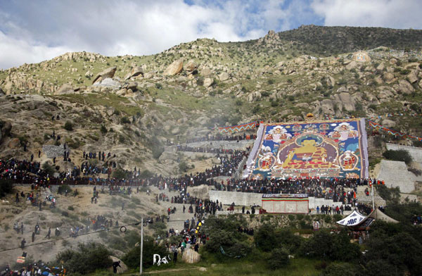 Tibetan Buddhists and tourists view a giant thangka, a religious silk embroidery or painting unique to Tibet, during the Shoton Festival at Drepung Monastery on the outskirts of Lhasa, Tibet autonomous region August 29, 2011.