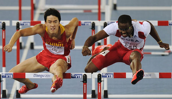 Cuba's Daron Robles(R), and China's Liu Xiang clear a gate as they compete in the men's 110m hurdles final at the World Athletics Championships in Daegu, South Korea, Monday, Aug. 29, 2011. Source:CFP