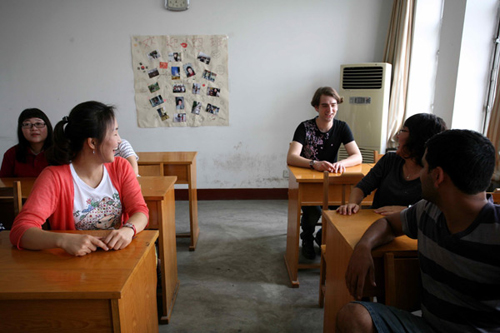 Roussillat Sebastien (third R), a 22-year-old French student at Shandong Normal University, talks to his classmates.