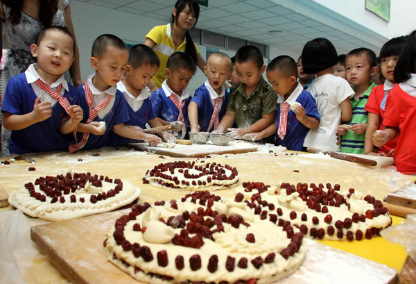 Children make moon cakes to celebrate the upcoming Mid-Autumn Festival in Beihai Kindergarten in Weifang, east China's Shandong Province, Sept. 7, 2011. Chinese people have the tradition to eat moon cakes on the Mid-Autumn Festival, which falls on Sept. 12 this year.