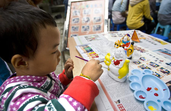A child paints on a rabbit doll at the Dongyue Temple in Beijing on Sept. 12, 2011, to celebrate the traditional Mid-autumn festival. Chinese people also have the tradition to eat mooncakes on the Mid-Autumn Festival.