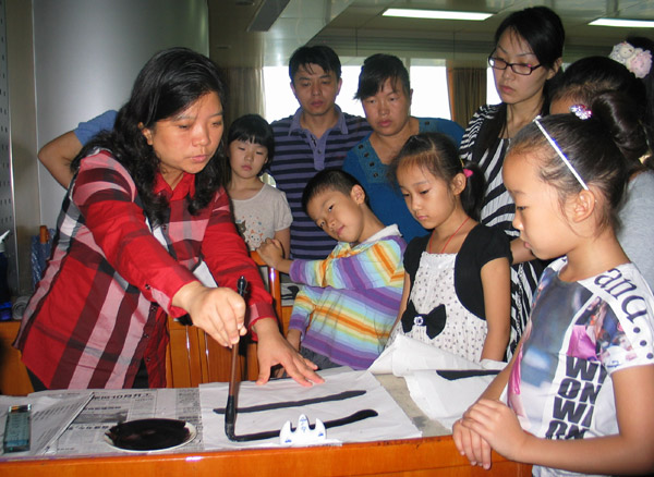 Wu Bin, 42, vice-chairwoman of Shandong Association for Young Calligraphers, teaches children calligraphy on Sept 4.