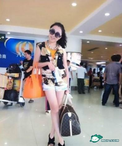 You Yixi holds two designer bags believed to be worth at least 100,000 yuan.