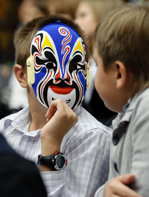 A student with a Chinese traditional mask talks to others during a Chinese language culture festival in Moscow, Russia, Sept. 24, 2011. A Chinese language culture festival was held in the 1948 School in Moscow, attracting Chinese middle school students and pupils living in Moscow and Russian students who loved Chinese culture to attend.