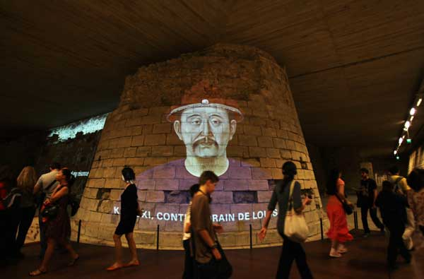 Visitors walk past a projective of the portrait of Emperor Kangxi in the Louvre Museum in Paris, capital of France, on Sept. 26, 2011. About 130 artifacts from the Forbidden City, China's ancient imperial palace museum, started to greet the French public in the Louvre Museum on Monday in an exhibition that will run until Jan. 9, 2012.