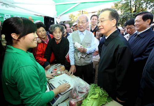 Chinese Premier Wen Jiabao (R, Front) talks with a vegetable vendor in Beihang Community in Beijing, capital of China, Oct. 1, 2011. Wen made an inspection tour early Saturday morning of a fresh vegetable market in the community that opens on weekends to sell vegetables directly to consumers. [Xinhua]