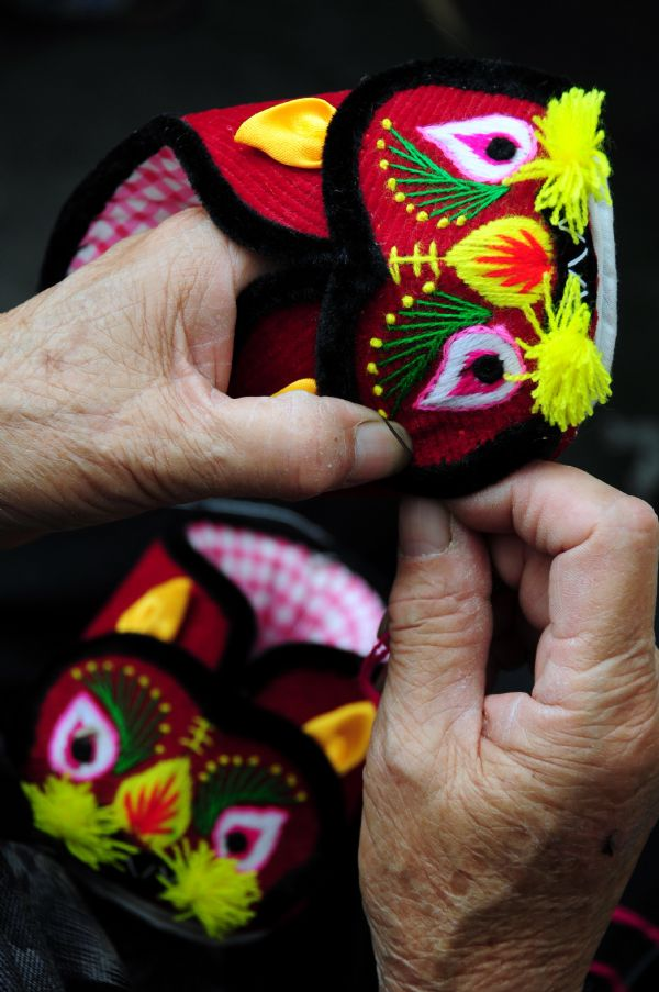 Gao Qinying works on a tiger boot in Tancheng County of Linyi City in east China's Shandong Province, Oct. 5, 2011.