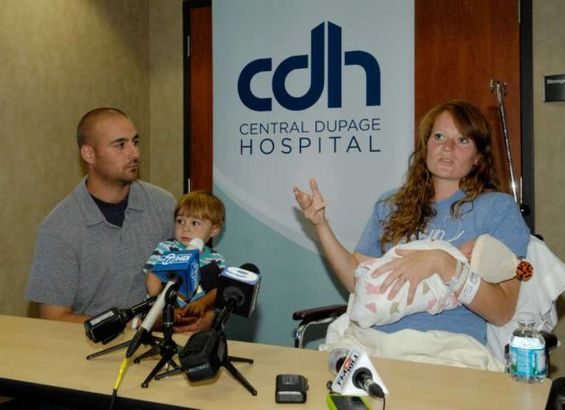 Amber Miller, of Westchester, Ill., gestures during a news conference as she holds her baby at Central DuPage Hospital in Winfield, Ill., Monday Oct. 10, 2011. [Agencies]