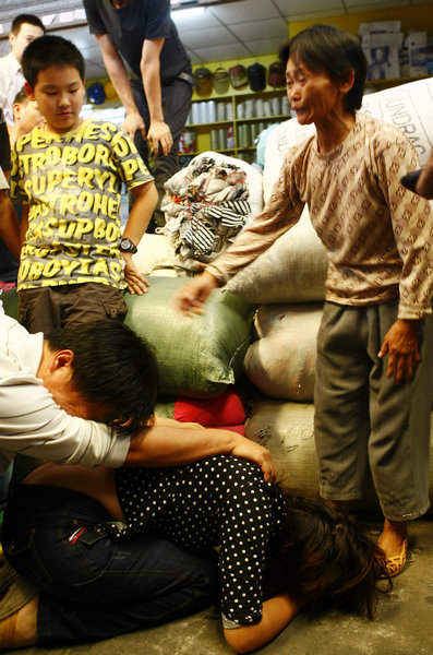 The parents of Yue Yue, a girl who had been run over by two vehicles, kneel down on Sunday to thank Chen Xianmei, who have moved their daughter to a safe place. [Provided to China Daily]