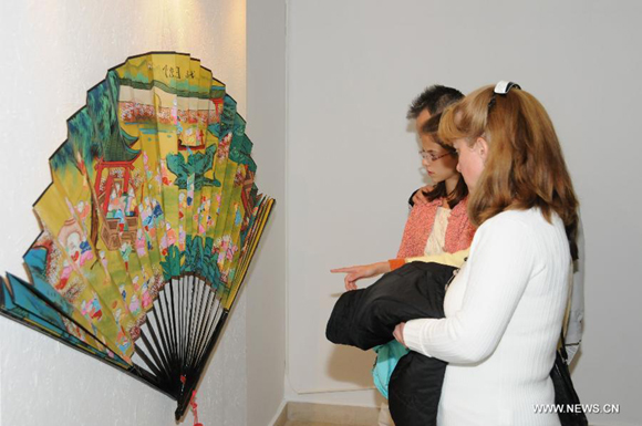 Visitors look at the fans displayed in an exhibition in the Romanian Peasant Museum in Bucharest, capital of Romania, October 17, 2011. The exhibition 'Art and craftsmanship in China - Umbrellas, Fans and Embroideries' opened on Monday and will show until Nov. 13.