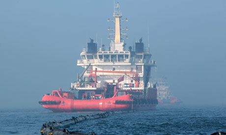 A ship cleans up the leaking oil near the platform C in the Bohai Sea, China.[CFP]