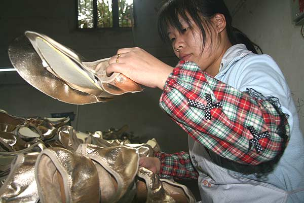 30-year-old Zhou Shuqing is examining the quality of shoes in a Baolilong shoe factory in Zhugao Town of Jintang County. She once worked in Guangdong for three years and returned home in 2008 to take care of her young child. [CnDG by Jiao Meng]