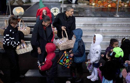 President Barack Obama and First Lady Michelle Obama welcome area students and the children of military families to the White House for trick-or-treating on Halloween. [Whitehouse.gov]