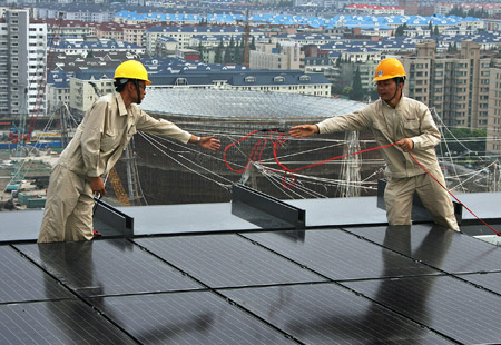 Workers fix solar energy panels on the top floor of the Chinese Pavilion at the Shanghai Expo Site, Shanghai, east China, July 25, 2009. 1,264 solar energy panels will be fixed on the top floor of the Chinese Pavilion, which could generate 300 kilowatt-hours of electricity per hour in the sunny days.