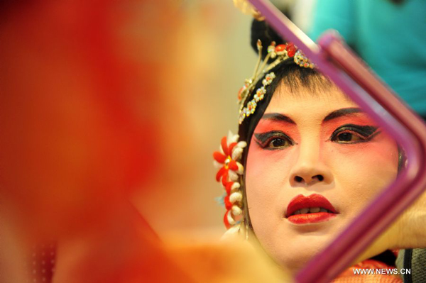 An amateur Peking Opera performer applies make-up backstage before a performance in Wuhan, central China's Hubei Province, Nov. 4, 2011. Dozens of Peking Opera fans from China and abroad held a show during the ongoing sixth Peking Opera Festival here Friday.