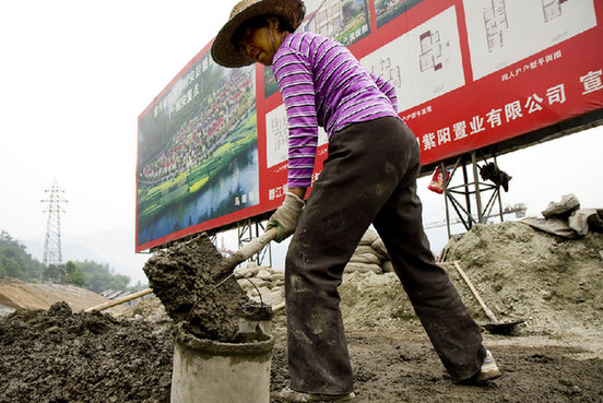 A worker in Wenchuan County, China, severely damaged by an earthquake in 2010, mixing cement at a new government-subsidized housing scheme. [un.org]