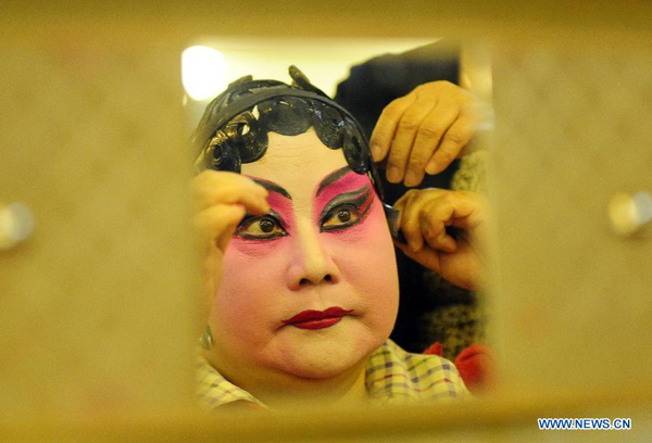 Qi Shufang, founder of Qi Shufang Peking Opera Troupe, makes a face-painting before performance during the 6th China Peking Opera Art Festival in Wuhan City, capital of central China's Hubei Province, Nov. 8, 2011.