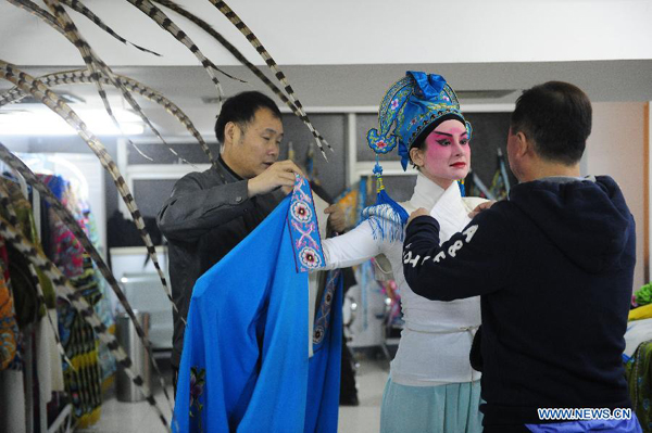 Lauren Engleman (C), a member of Qi Shufang Peking Opera Troupe, pulls on theatrical costume before performance during the 6th China Peking Opera Art Festival in Wuhan City, capital of central China's Hubei Province, Nov. 8, 2011.