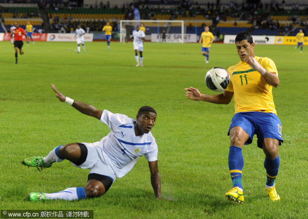 Brazil's Hulk (right) controls the ball past Gabon's Remy Ebanega during the inaugural match at the Gabonese Friendship stadium in Libreville, Gabon on Thursday, Nov. 10, 2011.