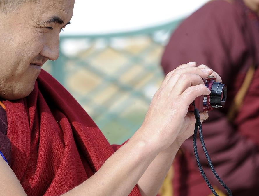 A lama takes photos for others at school in the Tibet College of Buddhism in Lhasa, capital of southwest China's Tibetan Autonomous Region, Nov. 7, 2011.