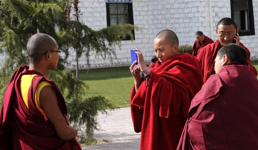 Lama students take photos for each other during a class break at school in the Tibet College of Buddhism in Lhasa, capital of southwest China's Tibetan Autonomous Region, Nov. 7, 2011.