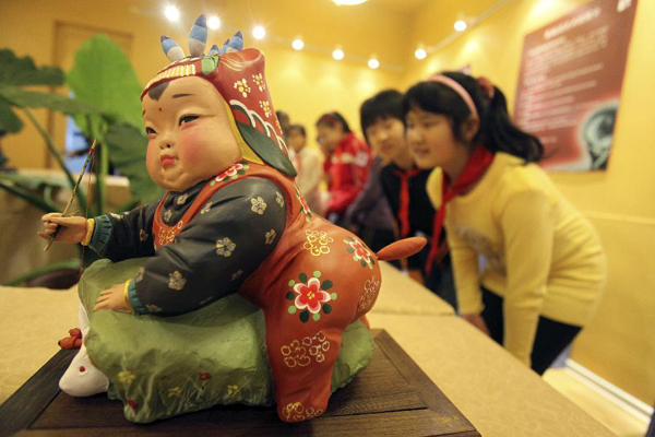 Students from Xinghua Primary School visit the exhibition of clay sculptor Zhang, in north China's Tianjin, Nov. 16, 2011. The first exhibition room of 'Clay figurine Zhang', the nation's non-material cultural heritage, opened in Xinghua Primary School.