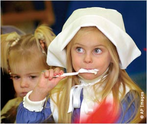 Dressed as a Pilgrim, a young girl enjoys a forkful of mashed potatoes at the Montessori Children's Center in Wheeling, West Virginia. [IIP Digital]