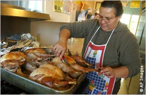 A woman inspects a batch of turkeys at Neighborhood House in Calexico, California, where hundreds of meals are served to needy families every Thanksgiving. [IIP Digital]