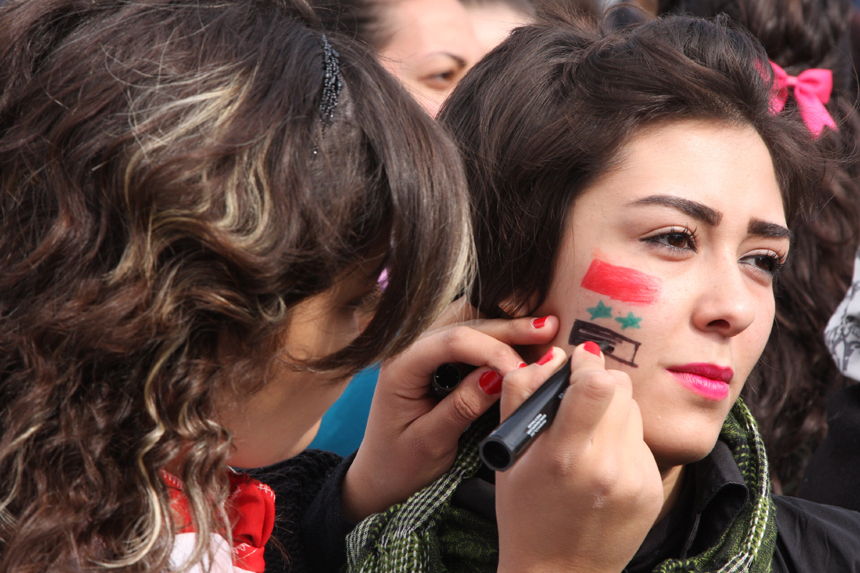 A Syrian woman paints the Syrian flag on the face of another woman during a rally held by thousands of Syrian women in the district of Bab Touma in Damascus, Syria, on Nov. 24, 2011.