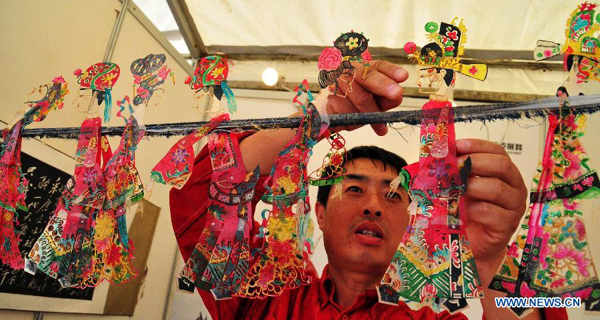An artist shows the puppetries for shadow puppetry performance in Nanning, capital of south China's Guangxi Zhuang Autonomous Region, Nov. 2, 2011.