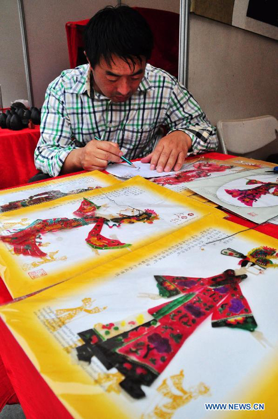 An artist makes puppetries for shadow puppetry performance in Nanning, capital of south China's Guangxi Zhuang Autonomous Region, Nov. 3, 2011. 