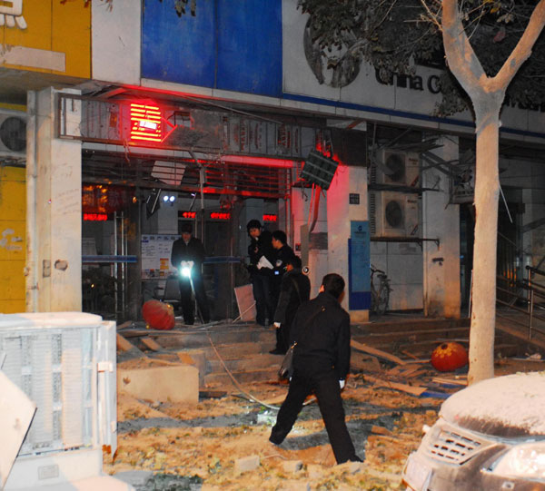 Police investigate the explosion site near a bank in Wuhan, Central China, Dec 1, 2011. [Photo/Xinhua]    