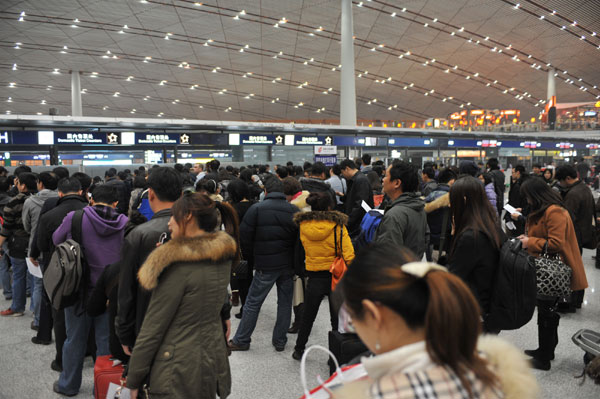 Passengers wait in the Terminal 3 at the Beijing Capital International Airport, Dec 4, 2011. [Photo/Xinhua]