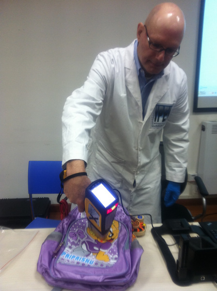 Joe DiGangi, a science and policy adviser for International POPs Elimination Network, which is a global network dedicated to eliminating persistent organic pollutants, uses an X-ray fluorescence to test the lead content of a schoolbag bought in Wuhan, Hubei province, during a news conference held by Greenpeace China on Wednesday in Beijing.