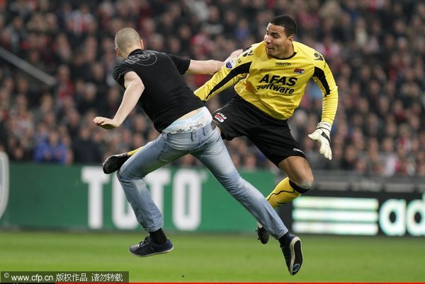 Goalkeeper Esteban Alvarado Brown (R) of AZ Alkmaar retaliates as he is attacked by a supporter during the Dutch cup match between Ajax and AZ Alkmaar at the Amsterdam Arena on December 22, 2011 in Amsterdam, Netherlands.