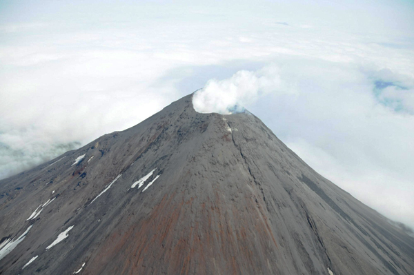 An aerial photograph shows the Cleveland Volcano during the time a small lava flow, or dome, was accumulating in the summit crater as the 660 foot (182.88m) wide summit crater emits a white, largely steam condensate cloud in this Aug 8, 2011 file photo. The remote volcano in Alaska's Aleutian islands erupted early on Dec 29, 2011 spouting an ash cloud 15,000 feet(4572m) into the sky and prompting an air-traffic alert, scientists said. [Photo/Agencies]