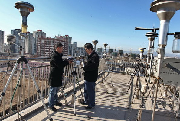 China National Environment Monitor Center (CNEMC) workers inspect PM2.5 - airborne pollutants smaller than 2.5 microns in diameter - monitoring equipment in Beijing on Jan 4, 2012. [CFP]