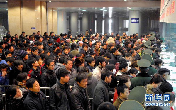 China's railways will carry 235 million passengers during the 40-day Spring Festival travel rush, up 6.1 percent year-on-year. In the picture, people are queuing for tickets at the Tianjin Railway Station on Jan. 5.