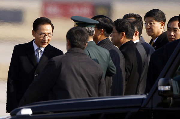 South Korean President Lee Myung-bak (L) shakes hands with officials after arriving at Beijing airport January 9, 2012. [Agencies]