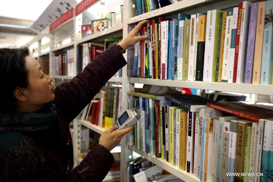 A dealer selects books during the 2012 Beijing Book Expo at the China International Exhibition Center in Beijing, capital of China, Jan. 9, 2012. A total of 762 publishing enterprises and book wholesalers participated in the four-day book expo. [Xinhua/Jin Liwang]