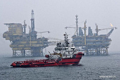 A ship moves near the platform B in Penglai 19-3 oilfield at north China's Bohai Bay, in this file photo taken on July 15, 2011. [Xinhua]