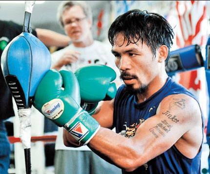 Manny Pacquiao works out as trainer Freddie Roach looks on at the Wild Card Boxing Club in the Hollywood section of Los Angeles.