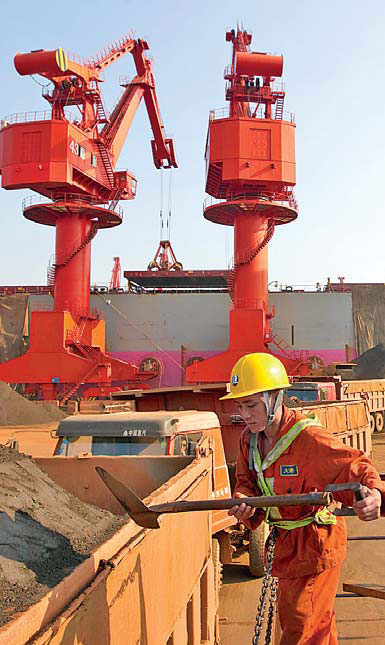Workers unload imported iron ore at Qingdao port, Shandong province. China launched a physical iron ore spot trading platform on Monday. [China Daily]