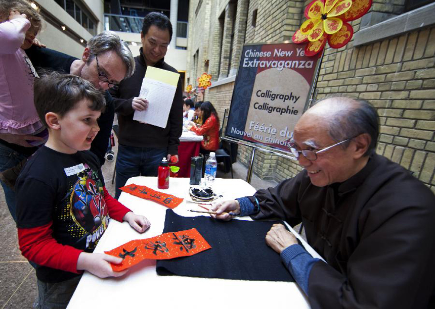A boy receives his Chinese name written in Chinese calligraphy during a Chinese New Year celebrating event held at the Royal Ontario Museum in Toronto, Canada, Jan. 15, 2012.