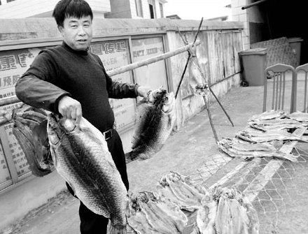 Zhang Chunshui, 54, prepares fish for drying in the open air in his yard in Datang village, Jiangxi province, last week. [China Daily]