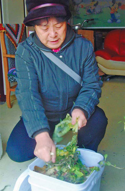 Sun Xiuli tosses vegetable leftovers into a bucket and sprinkles them with enzymes, as one of the participants of a garbage recycling project in Tianjin. [China Daily]