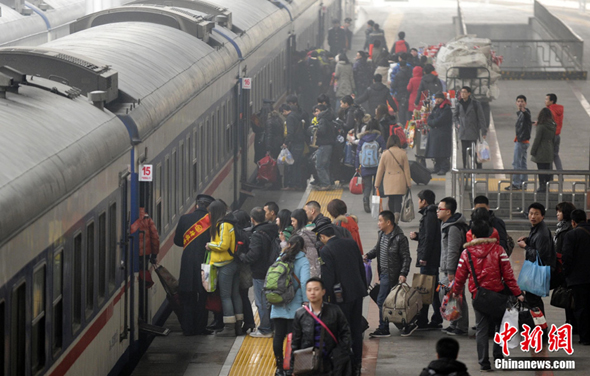 Passengers line up for getting on the train in Beijing West Railway Station on Jan. 19.