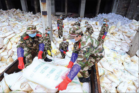 Police officers of Liuzhou, in the Guangxi Zhuang autonomous region, move bags of aluminum chloride, which can neutralize heavy metal pollutants, to ensure safe river water. A shortage of aluminum chloride in the city of Hechi could threaten the fight against the water's pollutant. [Xinhua]