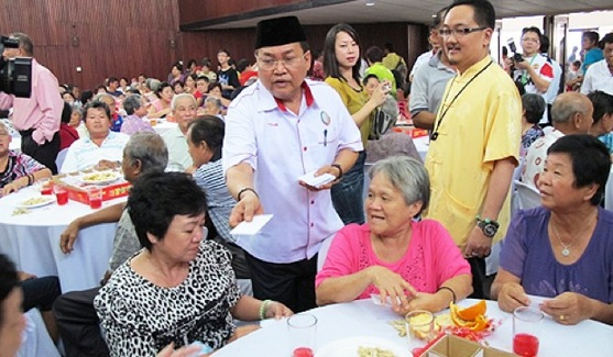 A Perkasa member hands white packets to Chinese at a Spring Festival gathering in Malaysia.
