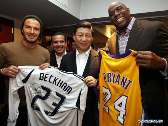 Chinese Vice President Xi Jinping (C, front) is presented with souvenir jerseys with names of Los Angeles Lakers star Kobe Bryant and Los Angeles Galaxy soccer player David Beckham at the Staples Center in Los Angeles, the United States, Feb. 17, 2012.